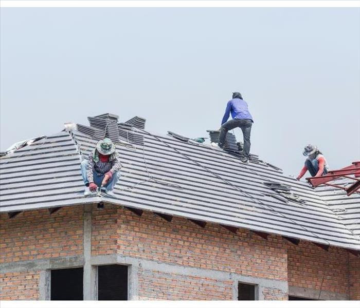 Workers performing maintenance to a commercial roof