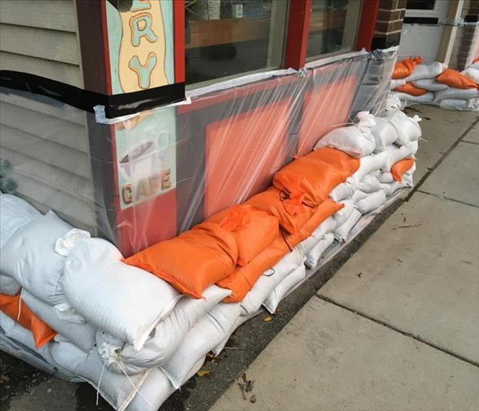 A business protected from flooding with sand bags and plastic film