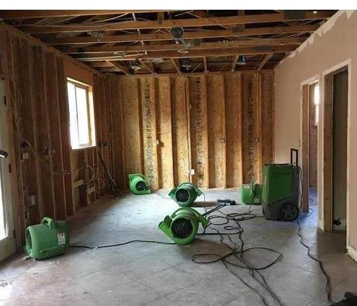 Drywalls from a room have been removed and also the ceiling, there are eight air scrubbers placed in different places